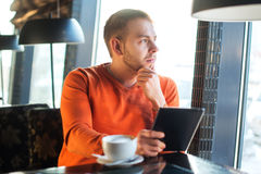 Handsome young man working with tablet,  thinking, looking out the window, while enjoying coffee in cafe Stock Photography