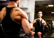 Handsome young man workout in fitness gym Stock Photos