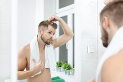 Handsome young man worried about hairloss. Handsome unshaven man looking into the mirror in bathroom Stock Photography