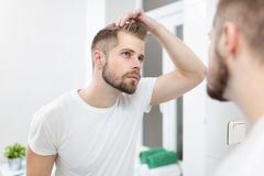 Handsome young man worried about hairloss. Handsome unshaven man looking into the mirror in bathroom Royalty Free Stock Photography