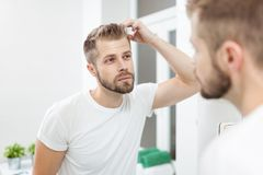 Handsome young man worried about hairloss. Handsome unshaven man looking into the mirror in bathroom Stock Photos