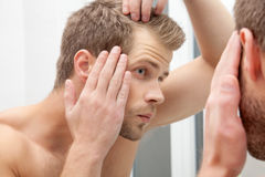 Handsome young man worried about hairloss. Handsome unshaven man looking into the mirror in bathroom Stock Photo