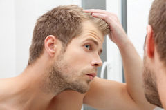 Handsome young man worried about hairloss. Handsome unshaven man looking into the mirror in bathroom Stock Images