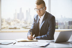 Handsome young man writing in notepad Royalty Free Stock Photos