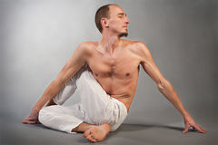 Handsome young man in yoga position. Studio portrait over gray background Stock Image