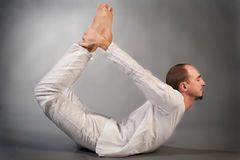 Handsome young man in yoga position. Studio portrait over gray background Royalty Free Stock Photography