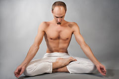 Handsome young man in yoga position. Studio portrait over gray background Stock Images