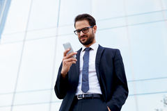 Handsome young manager of a large corporation is in the hands of the phone and smiling Royalty Free Stock Photo