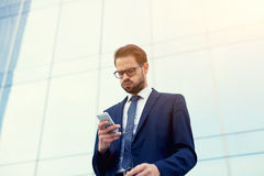 Handsome young manager of a large corporation has received a message from the boss on a mobile phone stock image