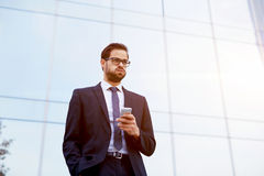 Handsome young manager of a large corporation has received a message from the boss on a mobile phone royalty free stock image
