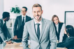 Handsome young manager looking at camera with blurred multicultural businesspeople. In conference hall stock photo