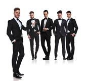 Handsome man in black tuxedo presents his elegant group stock photos