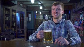 Man cheers with bartender. Handsome young men cheering with bartender at the pub. Attractive caucasian guy taking glass of lager from the bar counter. Male Stock Image