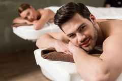 handsome young man looking at camera while having massage in spa stock image