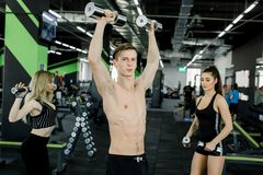 Handsome young man with muscular naked torso standing in the gym and trains biceps with dumbbells together with two royalty free stock image