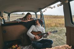 Do you like my new song?. Handsome young men playing guitar for his beautiful girlfriend while sitting in retro style mini van Stock Images