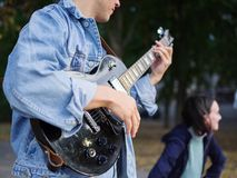 Young guy sings songs and plays guitar on a jeans jacket in a park on a natural background. Music concept. Handsome young men plays the guitar and sings songs stock photos