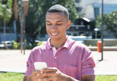 Handsome young mexican man messaging by phone. Outdoor in the city in the summer Stock Photo