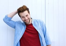 Handsome young modern man smiling with hand in hair Stock Photography