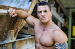 Handsome young muscle man with hand on rusty metal structure. Handsome young muscle man shirtless with hand on rusty metal structure, looking at camera royalty free stock photography