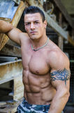 Handsome young muscle man with hand on rusty metal structure Stock Photos