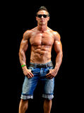 Handsome young muscle man naked wearing only jeans and sunglasses Stock Photography