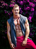 Handsome young muscle man smiling, outdoors, with open shirt. Attractive young muscle man smiling, outdoors, showing muscular pecs, abs, arms and torso Royalty Free Stock Photography