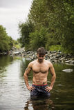 Handsome young muscle man standing in water pond, naked Stock Photo