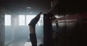 Handsome young muscular Caucasian man taking shirt off after workout in dark gym locker room, motivation spirit concept. Sporty male athlete after exercise stock video footage