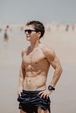 Handsome young muscular male model on the beach enjoying summer Royalty Free Stock Photos