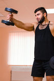 Handsome young muscular man exercising with dumbbells. Handsome young muscular man exercising with dumbbells Stock Photo