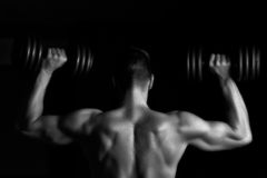 Handsome young muscular man lifting weights. Over dark background Royalty Free Stock Image