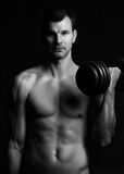 Handsome young muscular man lifting weights. Over dark background Royalty Free Stock Photos