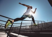 Handsome young muscular man in modern sport clothing run up the stairs outdoor at bright sunny day. Wide angle photo of royalty free stock photography