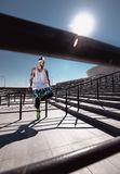 Handsome young muscular man in modern sport clothing sitting after training on the steps next to stadium at bright sunny royalty free stock photo