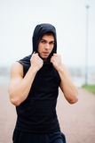 Handsome young muscular sports man on city park background, posing, Royalty Free Stock Image