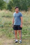 Handsome young muscular sports man exercising outside outdoor with rubber band. Stock Photos