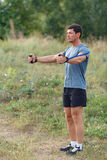 Handsome young muscular sports man exercising outside outdoor with rubber band. Royalty Free Stock Images