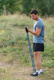 Handsome young muscular sports man exercising outside outdoor with rubber band. Royalty Free Stock Photo