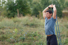 Handsome young muscular sports man exercising outside outdoor with rubber band. Stock Photography