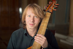 Handsome  young musician play viola da gamba in palace Stock Images