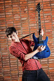 Handsome young musician playing the guitar Stock Photos