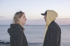 Handsome young natural and casual looking couple with hood jackets. With different expressions but still together turned to each other in profile at sunset on a stock photos