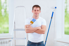 Handsome young painter with crossed arms holding blue paintbrush Stock Photos