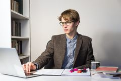 Handsome young person in reading eyeglasses at modern minimalistic workplace rests and turns away from table, looking up. Young male student works with books and Stock Image
