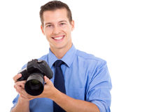 Handsome young photograher. Handsome young photographer holding a camera on white background stock photos