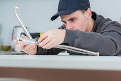 Handsome young plumber fixing tap at cleints home stock images