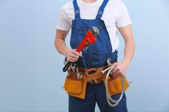 Handsome young plumber with tools. On color background Royalty Free Stock Photos