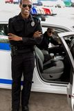 Handsome young policeman with crossed arms standing in front of. Police car royalty free stock photo