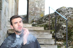 Handsome young priest smoking close up.  Stock Photo